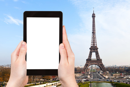 advertising logo: travel concept - tourist photograph eiffel tower from Trocadero in Paris on tablet pc with cut out screen with blank place for advertising logo