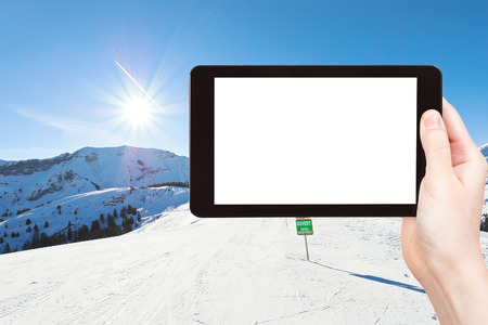 soleil: travel concept - tourist photograph skiing tracks on Alps mountains in Portes du Soleil region, Morzine - Avoriaz, France on tablet pc with cut out screen with blank place for advertising logo