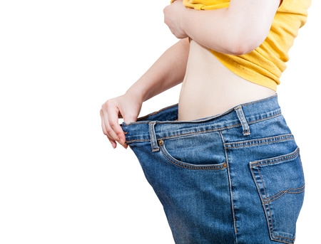 emaciated: emaciated girl trying on large size old jeans isolated on white background Stock Photo