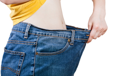 large size: thin girl trying on large size old denims isolated on white background