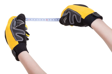 mensuration: worker hands in protective gloves with measuring tape isolated on white background