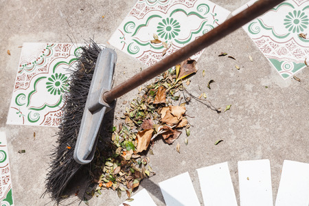 sweeps: brush sweeps fallen leaves from the concrete walkway