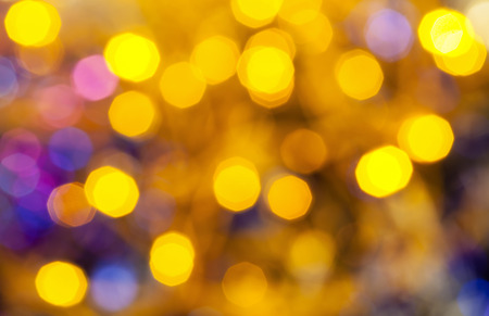 agleam: abstract blurred background - yellow and blue shimmering Christmas lights of electric garlands on Xmas tree