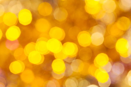agleam: abstract blurred background - colorful yellow shimmering Christmas lights of electric garlands on Xmas tree