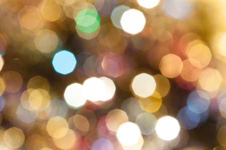 abstract blurred background - colorful brown shimmering Christmas lights of electric garlands on Xmas tree