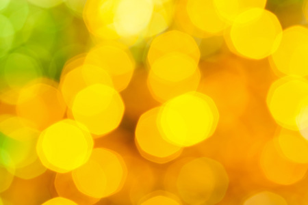 agleam: abstract blurred background - big yellow and green shimmering Christmas lights of electric garlands on Xmas tree