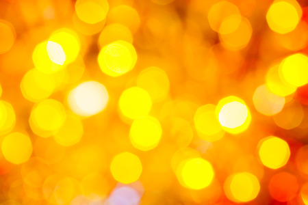 agleam: abstract blurred background - yellow and red shimmering Christmas lights of electric garlands on Xmas tree