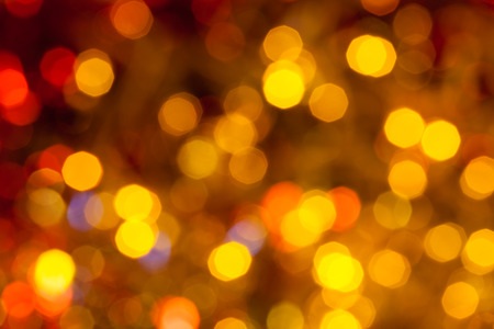 agleam: abstract blurred background - dark brown, yellow and red twinkling Christmas lights of electric garlands on Xmas tree Stock Photo