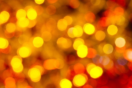 agleam: abstract blurred background - dark yellow and red flickering Christmas lights of electric garlands on Xmas tree Stock Photo