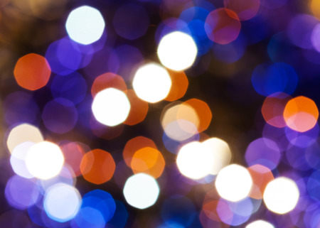 agleam: abstract blurred background - blue, red and violet shimmering Christmas lights of electric garlands on Xmas tree Stock Photo