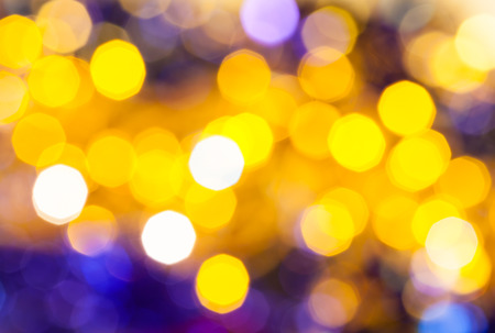 agleam: abstract blurred background - dark yellow and violet flickering Christmas lights of electric garlands on Xmas tree Stock Photo