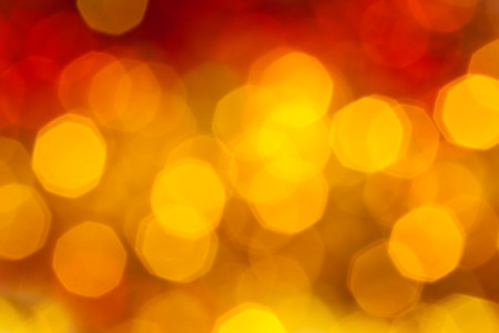 agleam: abstract blurred background - big yellow and red flickering Xmas lights of garlands on Christmas tree
