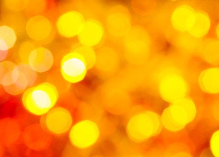 agleam: abstract blurred background - yellow and red twinkling Christmas lights of electric garlands on Xmas tree
