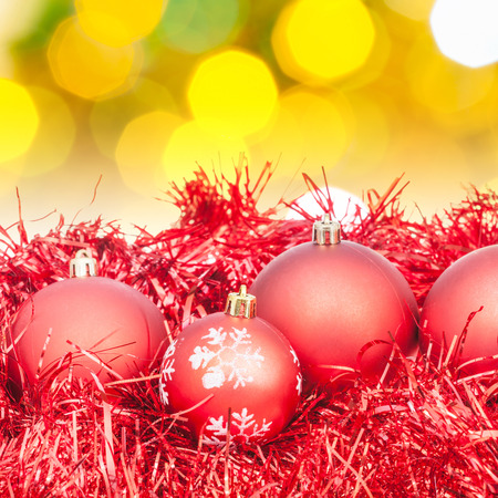 green christmas lights: Xmas still life - red balls, tinsel with blurred yellow and green Christmas lights background