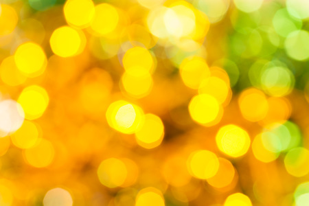 agleam: abstract blurred background - yellow and green shimmering Christmas lights of electric garlands on Xmas tree Stock Photo