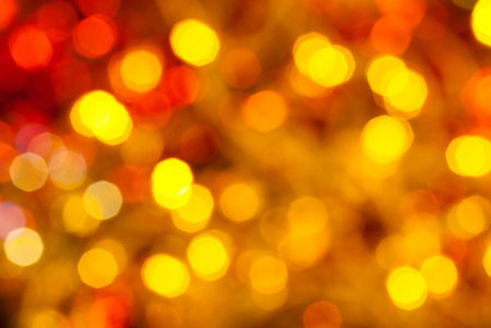 agleam: abstract blurred background - brown, yellow and red twinkling Christmas lights of electric garlands on Xmas tree