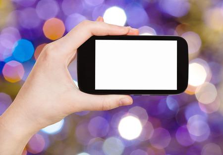 flickering: fiesta de navidad concepto - mano con el tel�fono inteligente con recorte de pantalla en el fondo del azul y violeta oscuro parpadeo luces de Navidad de guirnaldas el�ctricas en el �rbol de Navidad Foto de archivo
