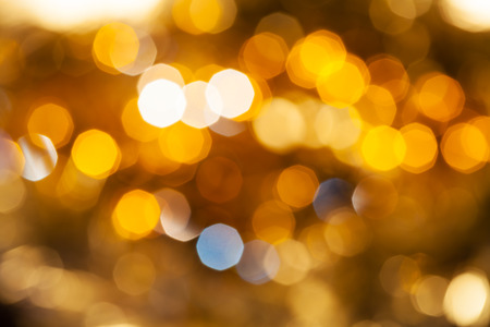 agleam: abstract blurred background - yellow and brown shimmering Christmas lights of electric garlands on Xmas tree