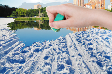 deletes: weather concept - hand deletes winter snow field by rubber eraser from image and summer cityscape are appearing