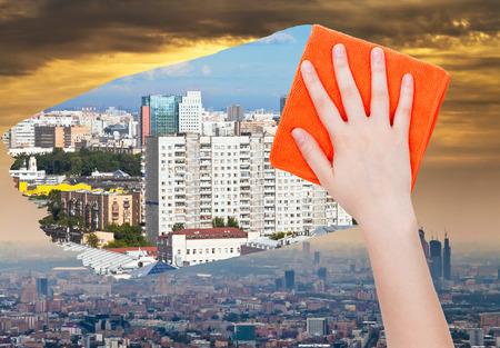 deletes: ecology concept - hand deletes smog in city by orange cloth from image and clear houses are appearing