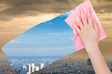 deletes: ecology concept - hand deletes smog in city by pink cloth from image and blue cityscape is appearing