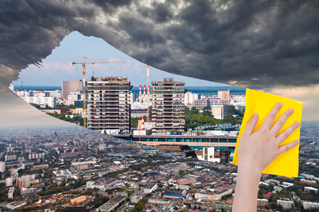 dark city: ecology concept - hand deletes dark city by yellow cloth from image and modern cityscape is appearing