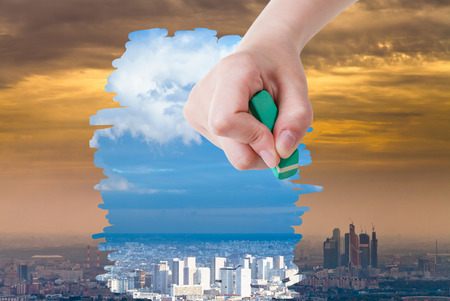 arise: weather concept - hand deletes smog urban landscape by eraser from image and clear blue city are appearing