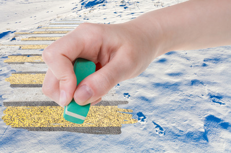 deletes: weather concept - hand deletes natural snow field by rubber eraser from image and modern urban road are appearing Stock Photo
