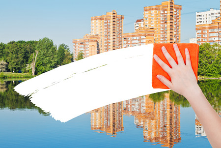 deletes: ecology concept - hand deletes new houses by orange rag from image and white empty copy space are appearing