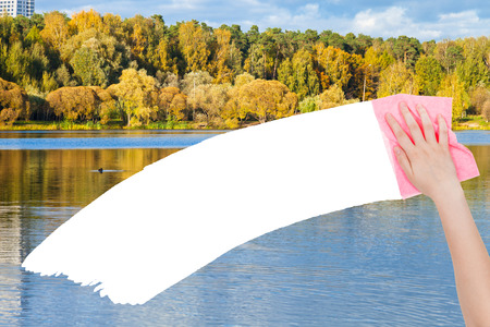 deletes: season concept - hand deletes autumn forest by pink rag from image and white empty copy space are appearing