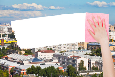 deletes: ecology concept - hand deletes urban houses by pink rag from image and white empty copy space are appearing
