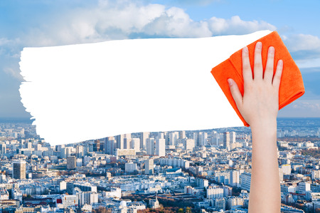 deletes: ecology concept - hand deletes blue city by orange rag from image and white empty copy space are appearing