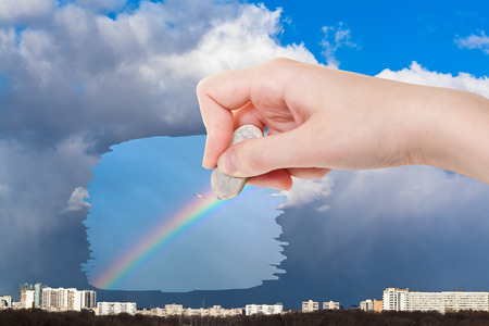 arise: weather concept - hand deletes rainy clouds over city by rubber eraser from image and rainbow and seagull in deep blue sky are appearing