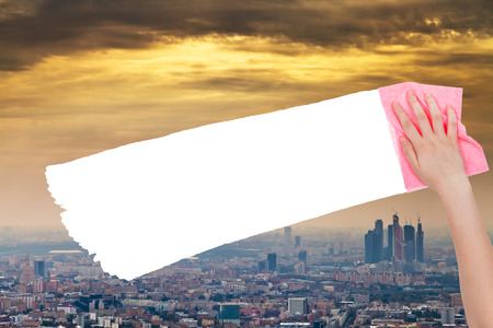 deletes: ecology concept - hand deletes smog sky over city by pink rag from image and white empty copy space are appearing