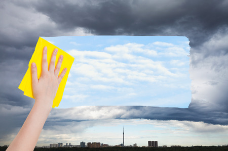 man arm: weather concept - hand deletes rainy clouds over city by yellow cloth from image and blue sky with white clouds are appearing