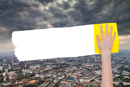 deletes: ecology concept - hand deletes storm clouds over city by yellow rag from image and white empty copy space are appearing