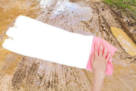 deletes: weather concept - hand deletes dirty country road by pink rag from image and white empty copy space are appearing Stock Photo