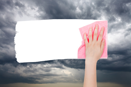 deletes: weather concept - hand deletes storm clouds on sky by pink rag from image and white empty copy space are appearing