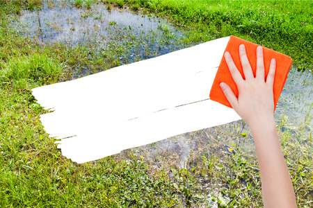 deletes: ecology concept - hand deletes swamp by orange rag from image and white empty copy space are appearing