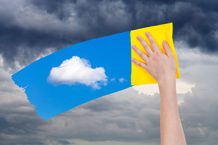 deletes: weather concept - hand deletes rain clouds by yellow cloth from image and blue sky with white cloud is appearing