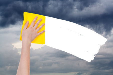 deletes: weather concept - hand deletes overcast sky by yellow rag from image and white empty copy space are appearing