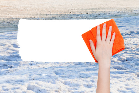 deletes: season concept - hand deletes winter snow by orange rag from image and white empty copy space are appearing Stock Photo