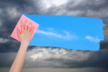 deletes: weather concept - hand deletes storm clouds by pink cloth from image and blue sky with white clouds are appearing Stock Photo