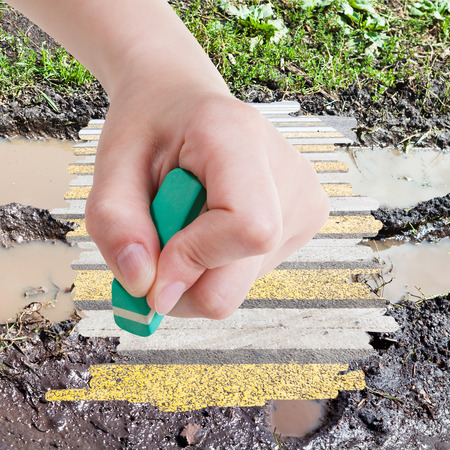 deletes: weather concept - hand deletes dirty road from image by rubber eraser and modern urban road are appearing