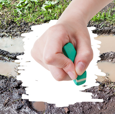deletes: weather concept - hand deletes mud from image of bad country road by rubber eraser Stock Photo