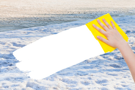 deletes: season concept - hand deletes white snow by yellow rag from image and white empty copy space are appearing