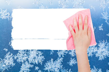 deletes: weather concept - hand deletes winter frosty pattern on window by pink rag from image and white empty copy space are appearing