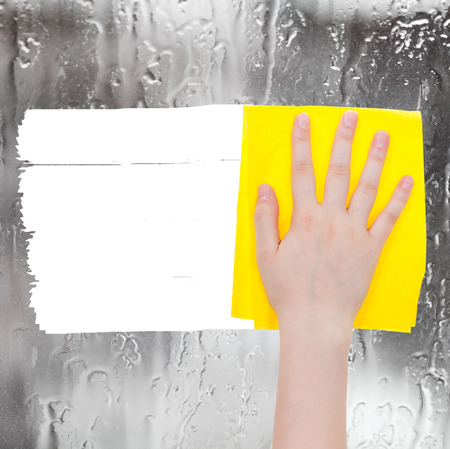 deletes: weather concept - hand deletes rainy water on window by yellow rag from image and white empty copy space are appearing