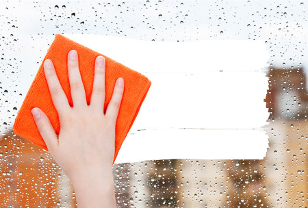 deletes: weather concept - hand deletes rain drops on window by orange rag from image and white empty copy space are appearing Stock Photo