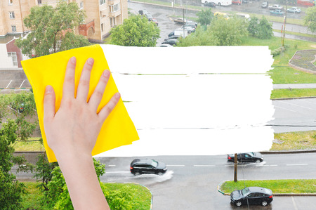 deletes: weather concept - hand deletes rain on street by yellow rag from image and white empty copy space are appearing